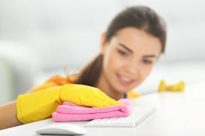 Eine Frau schütz ihre Haut vor Putzmitteln mit Handschuhen