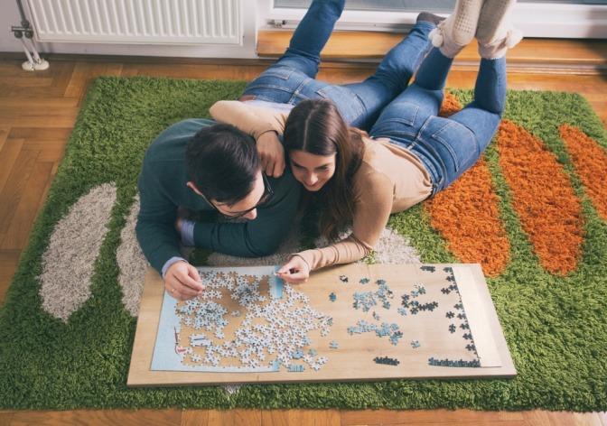 Ein Mann und eine Frau bauen ein Puzzle als Hobby