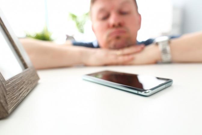 Ein Handy liegt auf dem Tisch. Ein nachdenklicher Mann im Hintergrund wartet auf einen Anruf odereine Nachricht einer Frau.