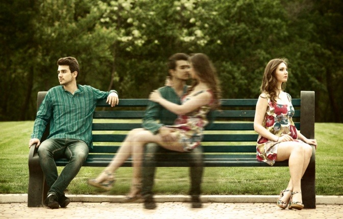 Ein Mann und seine Partnerin kuscheln sich auf einer Parkbank aneinander.