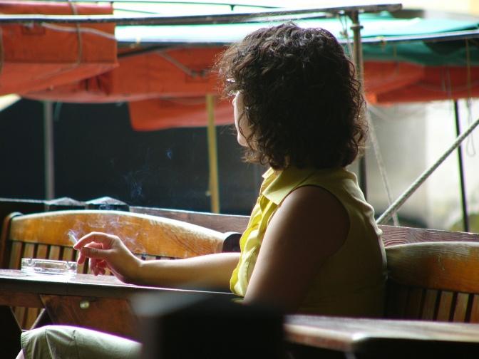 Eine Frau sitzt aus Gewohnheit beim Tisch und raucht