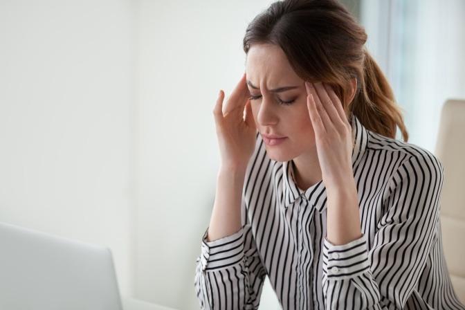 Eine Frau hat Kopfschmerzen wegen schlechtem Raumklima
