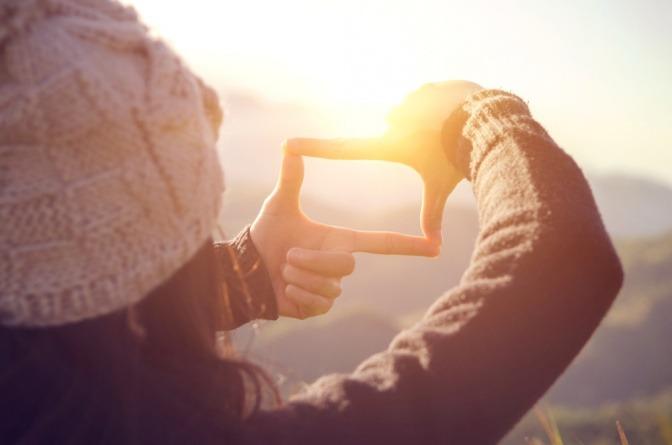 Hände einer Frau machen Rahmen um Sonnenaufgang auf Berg.