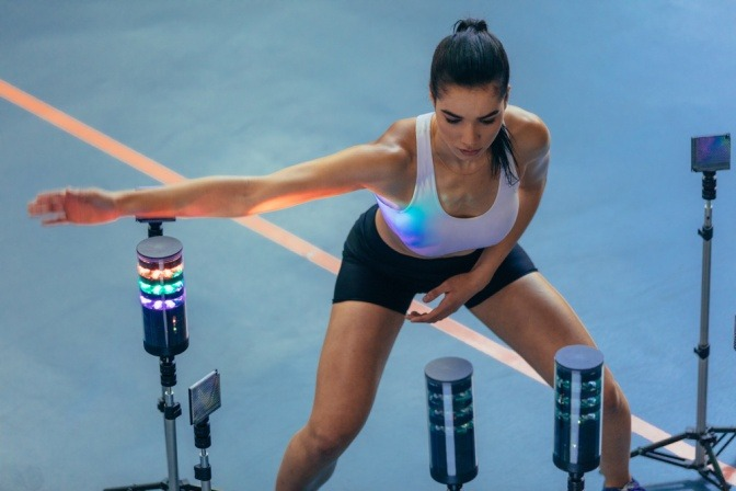 Weibliche Athletin mit visuellen Stimulus-System, mit dem man Reaktionsgeschwindigkeit verbessern kann.
