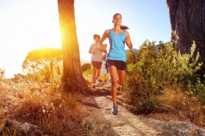 Frau beim Trail-Running im Wald um Reaktion zu verbessern