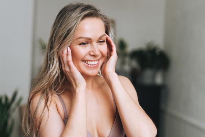 Eine Frau hat reine Haut im Gesicht und ist glücklich