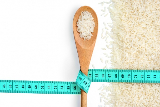 Reis zum Abnehmen auf einem Löffel mit einem Maßband