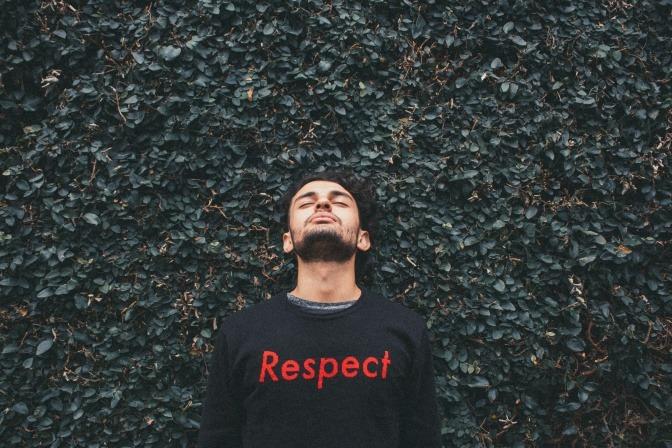 """Ein Mann liegt auf einer Wiese, auf seinem Pullover steht in großen Lettern """"RESPEKT""""."""
