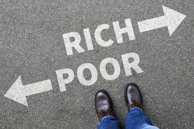 Auf dem Asphalt ist die Aufschrift rich poor zu sehen