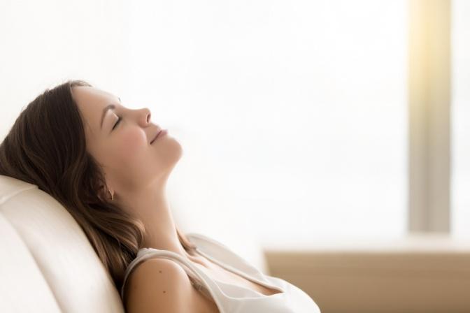 Frau mit geschlossenen Augen im Profil lehnt sich entspannt zurück
