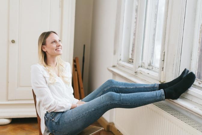 Frau vor Heizkörper bei Fenster