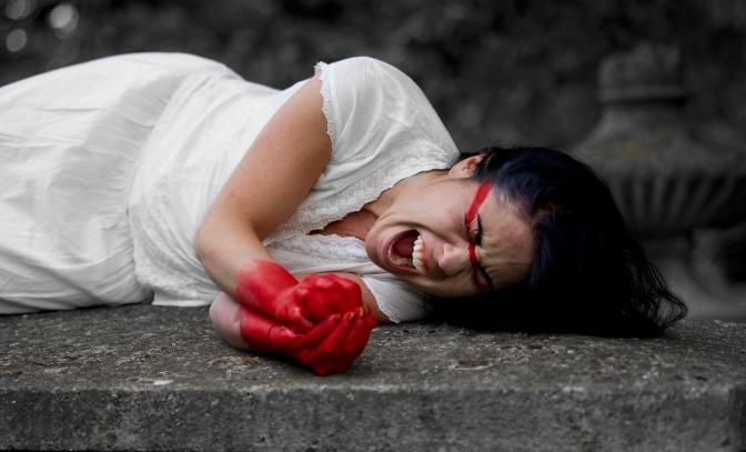 Eine Frau in einem weißen Kleid liegt auf dem Boden und schreit.