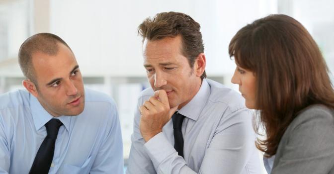 Drei Menschen sitzen nebeneinander zum Fragen stellen