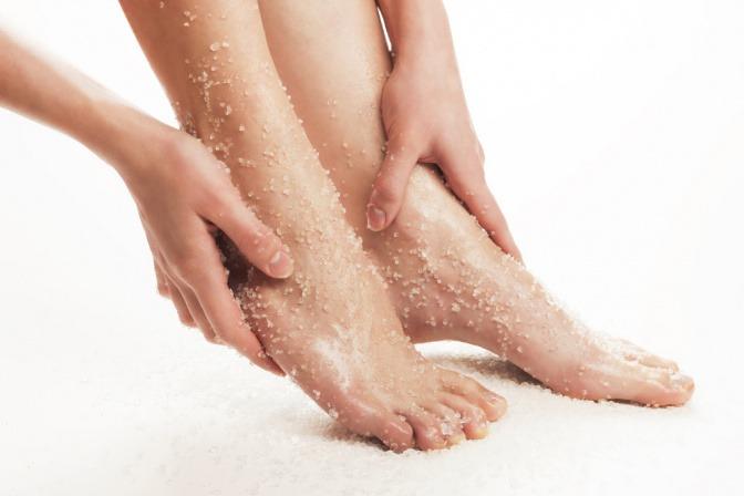 Eine Frau trägt ein Peeling auf ihre Füße auf.