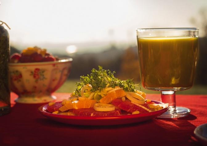Ein Glas mit Smoothie steht neben einem Teller mit Rohkost