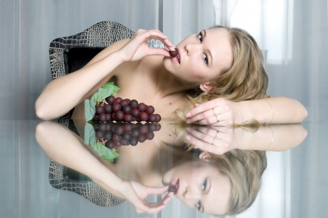 Eine Frau sitzt an einem großen Esstisch und nascht an ein paar Weintrauben.