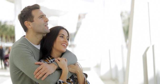 Ein Paar liegt sich in den Armen und betrachtet gemeinsam etwas.