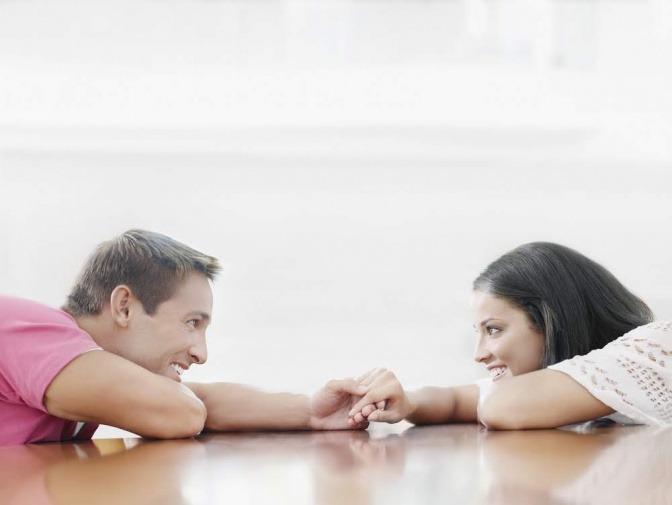 Ein Paar liegt bäuchlings auf dem Boden und die Partner blicken sich an.
