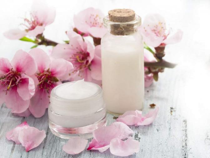 Rosenblüten liegen neben einem Kosmetik-Tiegel