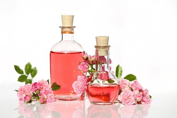 Neben Blüten von Rosen sind Fläschchen mit Rosenwasser