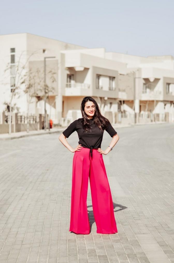 Eine Frau trägt rote Marlenehosen
