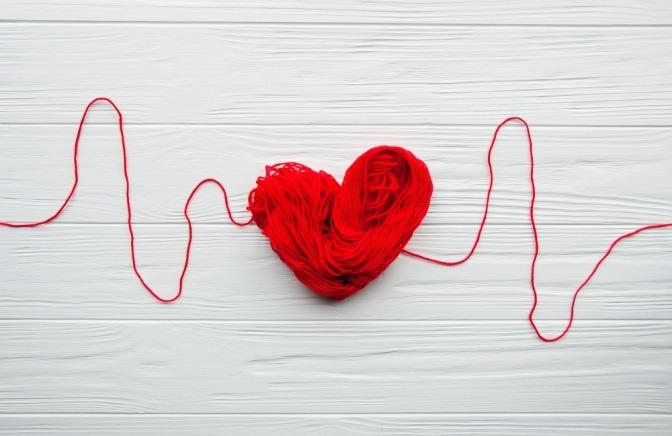 Roter Faden der sich in der Mitte zu einem Herz formt
