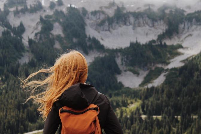 Rothaarige junge Frau in der Natur mit Rücksack