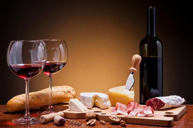 Zwei Gläser Rotwein stehen neben Käse und Wurst