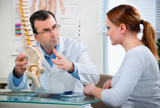 Arzt erklärt einer Frau die Wirbelsäule