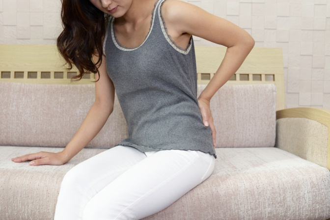 Eine Frau mit Rückenschmerzen sitzt am Bett
