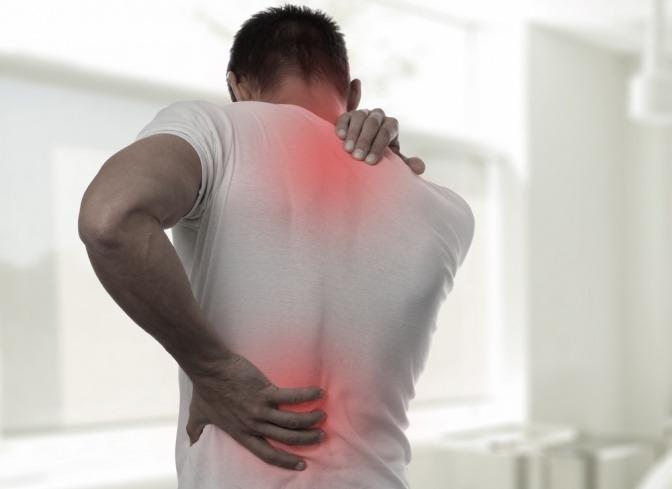 Die Rückenschmerzen eines Mannes sind an seiner Wirbelsäule rot eingezeichnet