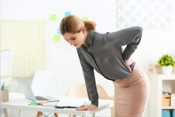 Eine Frau scheint Rückenschmerzen zu haben