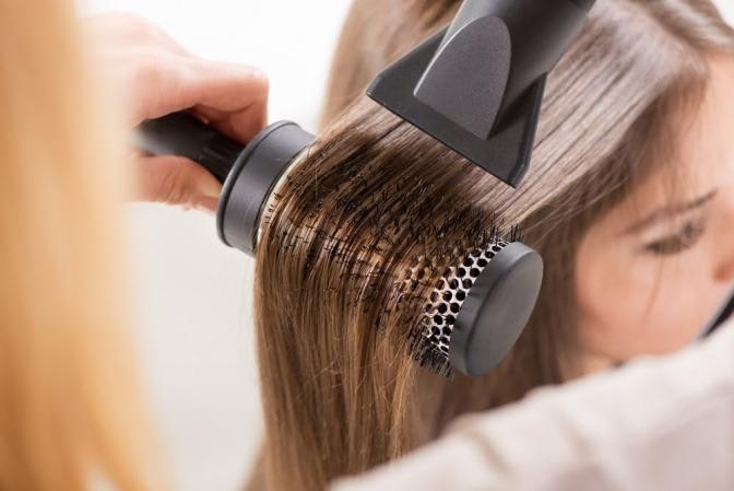 Eine Frau will mit einer Rundbürste und Föhn Haare glätten