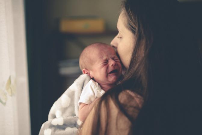 Ein Säugling weint im Arm seiner Mutter