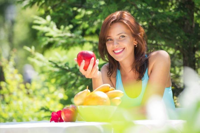 Eine Frau hält im Frühling einen Apfel für eine Säure-Basen-Haushalt Ernährung