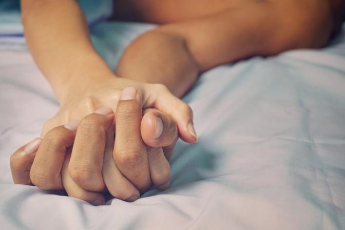 Paar im Bett mit verschränkten Händen