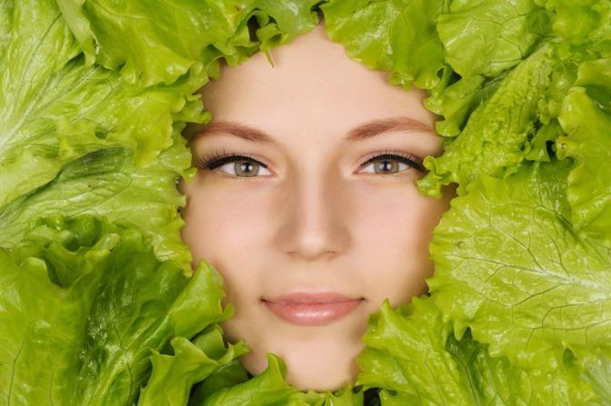 Das Gesicht einer Frau ist mit grünem Salat umrandet