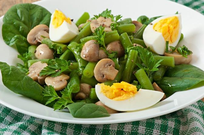 Ein Salat mit Pilzen und Eiern ist angerichtet