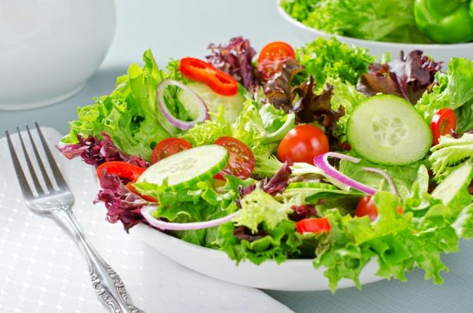Eine Gabel liegt neben einem Teller mit Salat