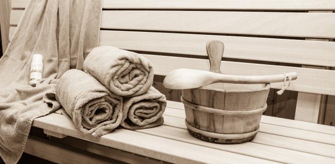 Auf einer Saunabank liegt Saunazubehör und Handtücher