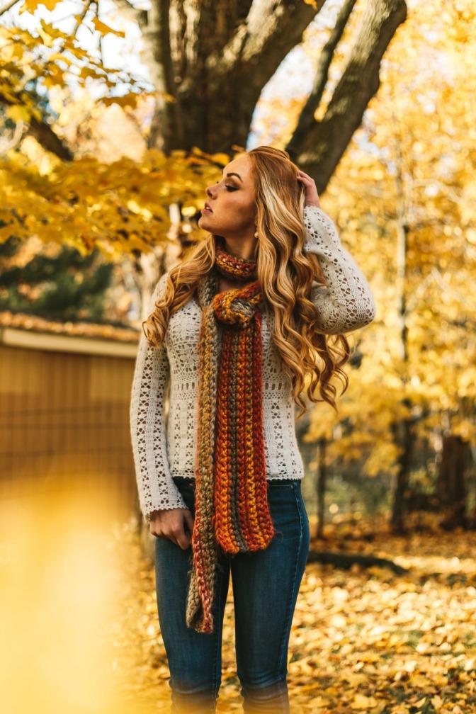 Eine Frau hat einen Schal vorne verknotet