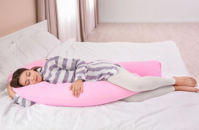 Eine Schwangere liegt in Seitenlage mit einem Stillkissen als Stütze