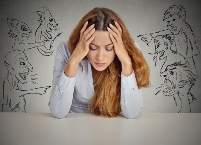 Karikaturen von bösen und selbstschädigenden Gedanken zeigen spöttisch auf eine zusammengekauert am Schreibtisch sitzende Frau.