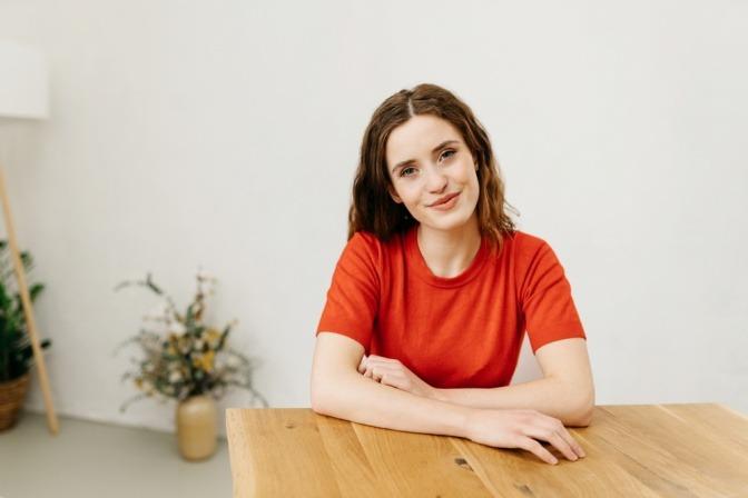 Eine junge Frau blickt mit einem ruhigen Lächeln in die Kamera, während sie an einem Tisch sitzt. Sie wirkt nachdenklich und selbstsicher.
