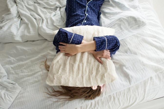 Eine Frau hält sich im Bett ein Kissen über den Kopf