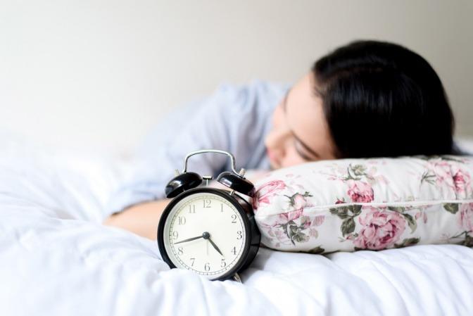 Frau im Bett vor einem analogem Wecker.