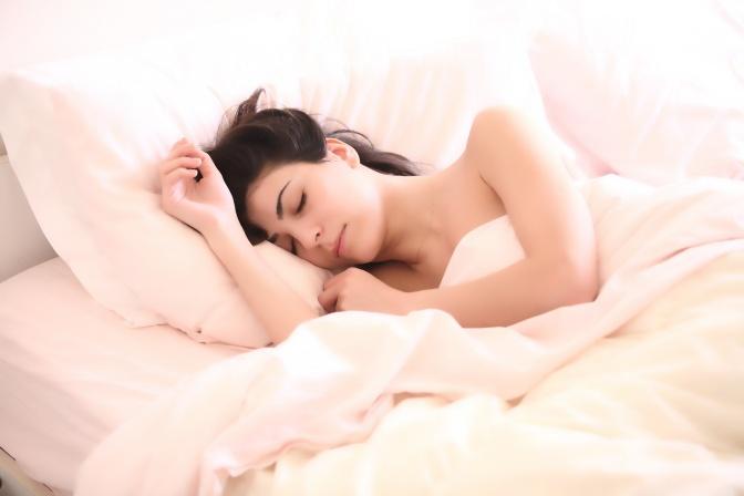 Eine Frau liegt im Bett und schläft vollkommen entspannt