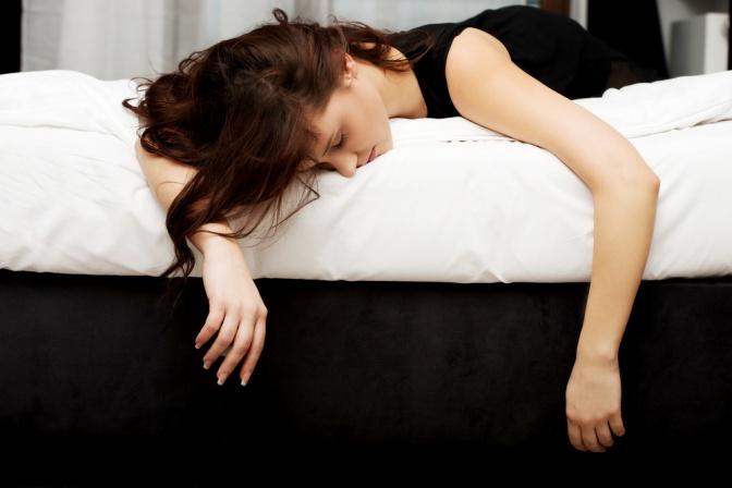 Eine Frau liegt am Bett und lässt alles hängen