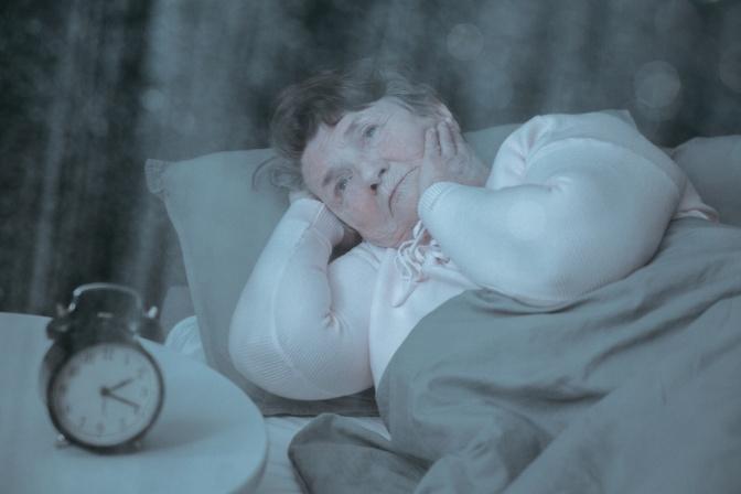Eine alte Frau liegt mit Schlafstörungen im Bett