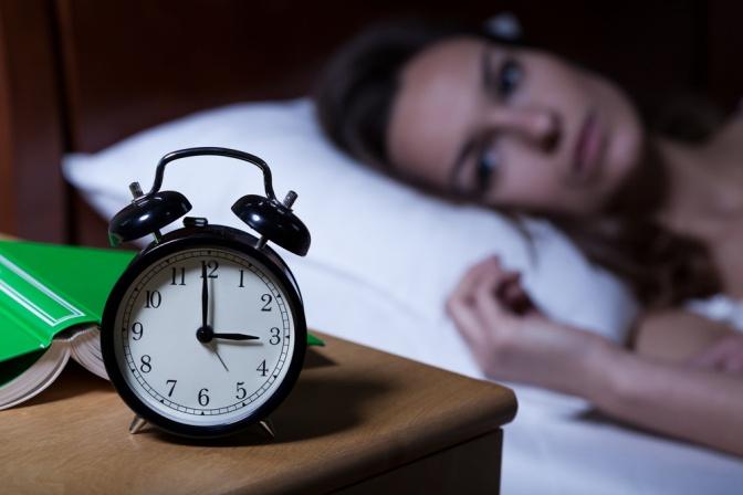 Eine Frau leidet unter Schlafstörungen und sieht auf den Wecker